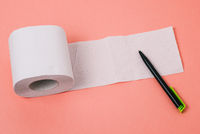 Empty white sheet on a pink background with pen. Expanded roll of toilet paper. Free space for text. Top view, copy space.