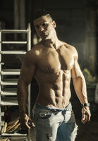Muscular young latino man shirtless in jeans indoors