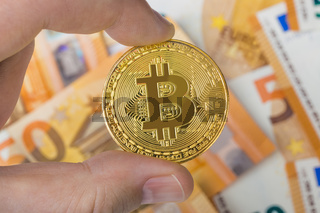 Hand with bitcoin and money - business background