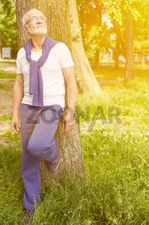 Senior mit Brille lehnt an Baum