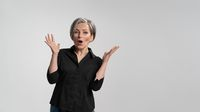 Grey haired mature woman doing a amazement gesture.Pretty mid aged grey haired woman in black shirt isolated on grey background. Human emotions, facial expression concept