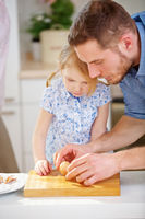 Vater zeigt Tochter wie ein Ei geschält wird