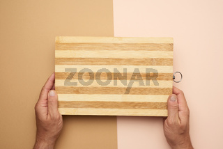 two male hands hold an empty new brown wooden cutting board