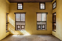 Facade of two Interleaved wooden ornate windows - Mashrabiya - in stone wall