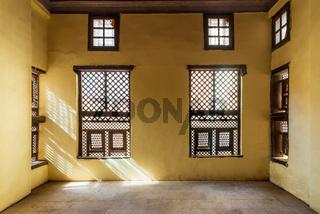 Facade of two Interleaved wooden ornate windows - Mashrabiya - in stone wall