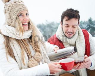 Frau neben Mann gießt Tee ein