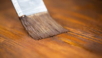 Close-up of paintbrush applying brown color on wooden table.