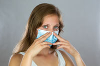 Young woman holding a surgical mask on the nose.