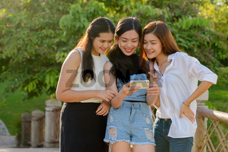 Three young Asian women as friends using phone together at the park
