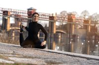 Portrait of sports girl doing yoga stretching exercise on the riverside