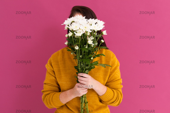 Caucasian woman covering her face with bouquet of white flowers on pink