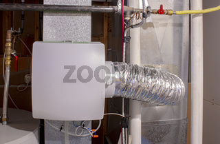 A home humidifier attached to the return duct with a bypass connection to the supply hot air duct.