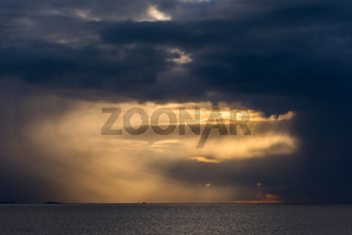 Massive storm clouds over open sea with streaks of light coming through