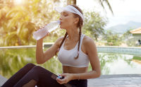 Sporty female drinking water during workout