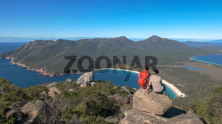a young couple looking towards wineglass bay from mt amos
