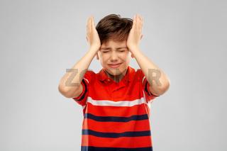 stressed boy in red polo t-shirt having headache