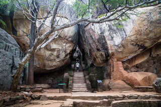 Tourists walking on stairs between two huge stones in Sigiriya, Sri Lanka