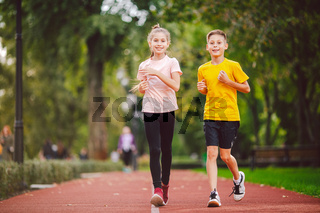 Sports and fitness in adolescence. Caucasian twins boy and girl run on the jogging track in the city park. Two children brother and sister for 10 years running on a rubberized outdoor treadmill