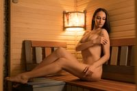Sexy nude woman in sauna full-length view