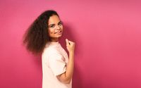 Beautiful young African American girl half turned looking positively at camera wearing peachy t-shirt showing her muscles isolated on pink background. Beauty concept