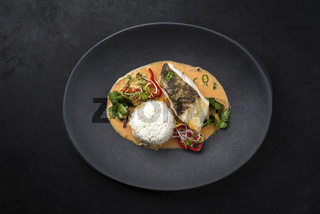 Gourmet fried skrei cod fish Thai curry with jasmine rice and chili as top view on a modern design plate with copy space