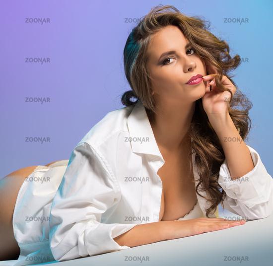 Coquettish young brunette posing lying in studio