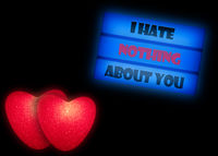 Two illuminated red hearts and a cinema light box with the text I HATE NOTHING ABOUT YOU isolated on