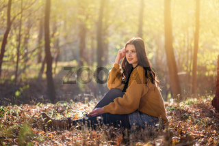 Young beautiful caucasian woman sits on the ground in a autumn park among high trees. Good sunny day it is great opportunity for relaxation and harmony with nature