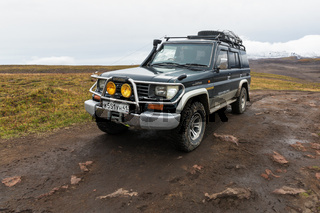 Off-road expedition car Toyota Land Cruiser Prado parked on mountain road