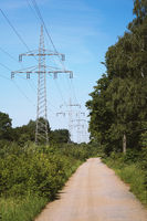 transmission line or overhead power cable along rural dirt track path through countryside