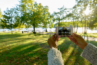 Hands of mature woman taking picture with phone at the park