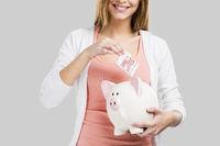 Beautiful woman putting money in a piggy bank