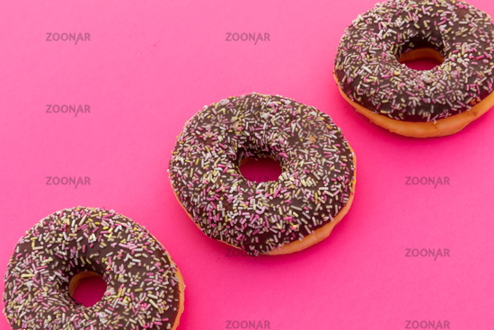 High angle view of three chocolate donuts with sprinkles on pink background