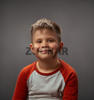 Little boy toddler adorable cute portrait. Smiling little boy full of happy feelings. Portrait, isolated over grey background. Facial expressions, emotions, feelings