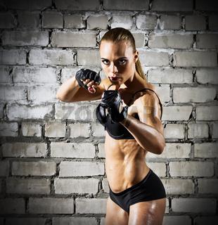 Muscular woman on grey brick wall (dark version)