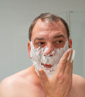 Male in front of a mirror while shaving a beard and facial care