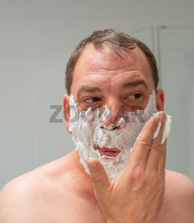 Mann vor einem Spiegel beim Bart rasieren und Gesichtspflege