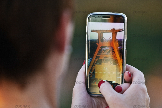 Woman photographs with the cell phone the head frame of the Zeche Zollverein, Essen, Germany