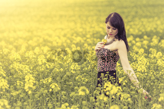 Beautiful woman in meadow of yellow flowers touching flower