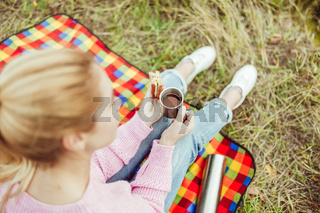 Charming blonde eats sandwich and drinks tea sitting on picnic blanket at grass. Focus on female hands. Close up shot, high angle view. Snack in nature outdoors concept
