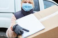 Paketbotin mit Mundschutz bittet um Unterschrift