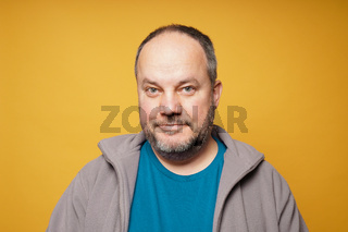 casual chubby mature man against yellow background