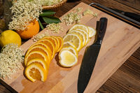 A cutting board with a kitchen knife and a sliced organic lemon and organic orange and elderflower