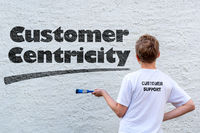 Pupil in front of a white house wall with the text CUSTOMER CENTRICITY