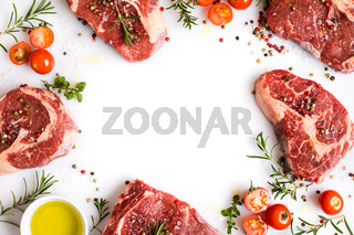 raw ribeye steaks with different spices and olive oil