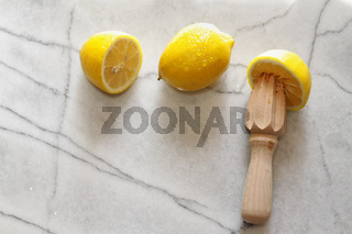 Fresh lemons and citrus reamer on marble