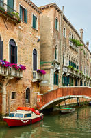 Venetian canal with bridge and moored motorboat
