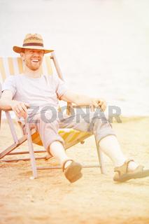 Mann sitzt im Liegestuhl im Sommer