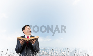 Surprised businessman holding open old book