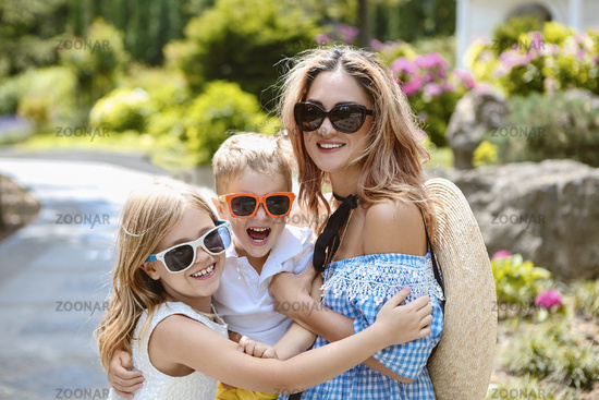 Young beautiful mother walking her little son and daughter outdoors.